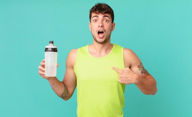 Fitness man die geschokt en verrast kijkt met wijd open mond, wijzend naar zichzelf