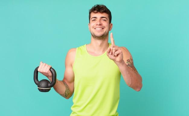 Fitness man die trots en zelfverzekerd glimlacht en nummer één triomfantelijk poseert en zich een leider voelt