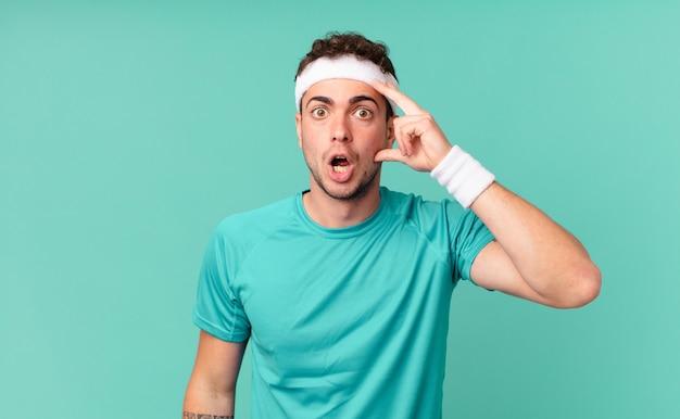 Fitness man die verrast, met open mond, geschokt kijkt en een nieuwe gedachte, idee of concept realiseert