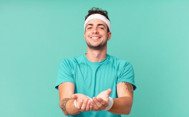 Fitness man die vrolijk lacht met een vriendelijke, zelfverzekerde, positieve blik, een object of concept aanbiedt en toont