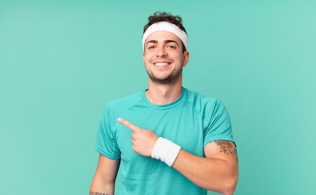 Fitness man die vrolijk lacht, zich gelukkig voelt en naar de zijkant en naar boven wijst, een object in de kopieerruimte laat zien