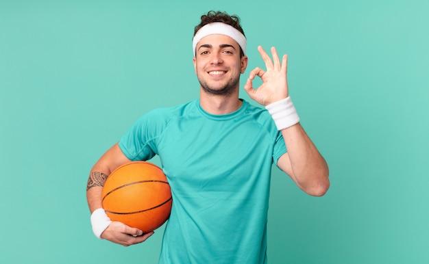 Fitness man die zich gelukkig, ontspannen en tevreden voelt, goedkeuring toont met een goed gebaar, glimlachend