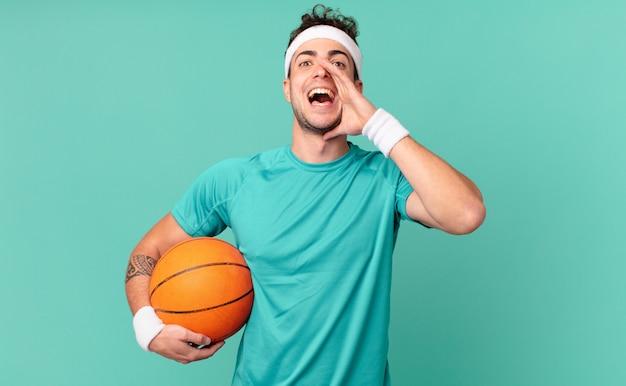 Fitness man die zich gelukkig, opgewonden en positief voelt, een grote schreeuw geeft met de handen naast de mond, roept