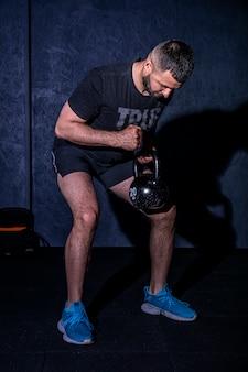 Fitness man doet een krachttraining door zware kettlebell op te heffen.