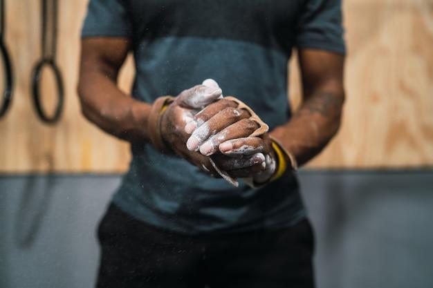 Fitness man handen wrijven met krijt magnesium poeder.