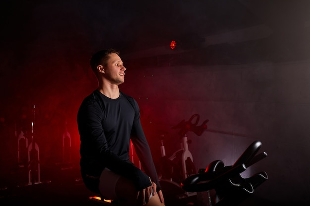 Fitness man hebben rust na een training op de fiets in de sportschool, ontspannen, in sportieve kleding
