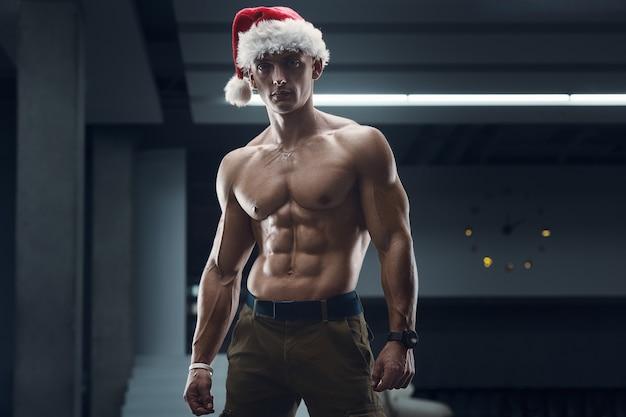 Fitness man in kerstman hoed kostuum in sportschool met mobiele telefoon.