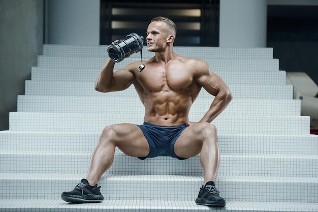 Fitness man in sportschool drinkwater na training
