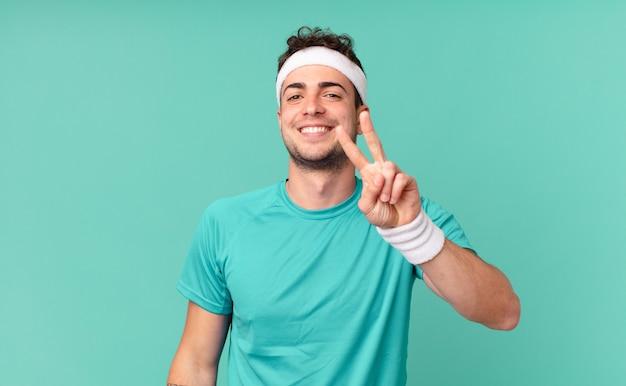 Fitness man lacht en ziet er gelukkig, zorgeloos en positief uit, gebaart overwinning of vrede met één hand