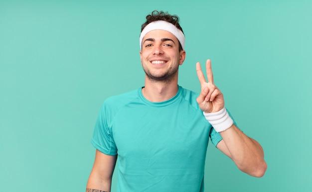 Fitness man lacht en ziet er vriendelijk uit, toont nummer twee of seconde met de hand naar voren, aftellend