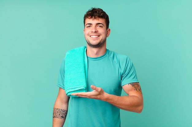 Fitness man lacht vrolijk, voelt zich gelukkig en toont een concept in kopieerruimte met palm van hand