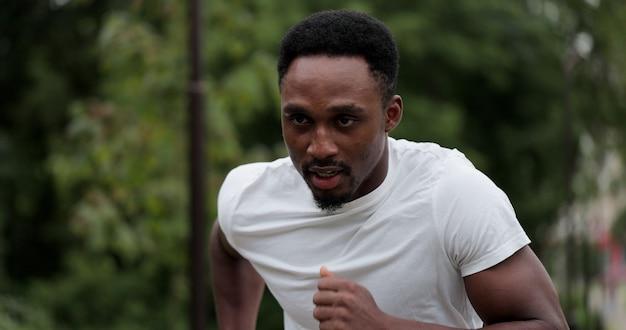 Fitness man loopt buiten op park straat. jonge zwarte man in fitness slijtage en hardlopen in het park 's ochtends. gezond levensstijlconcept.