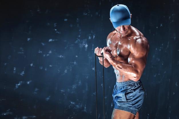 Fitness man met elastische banden met donkere muur.