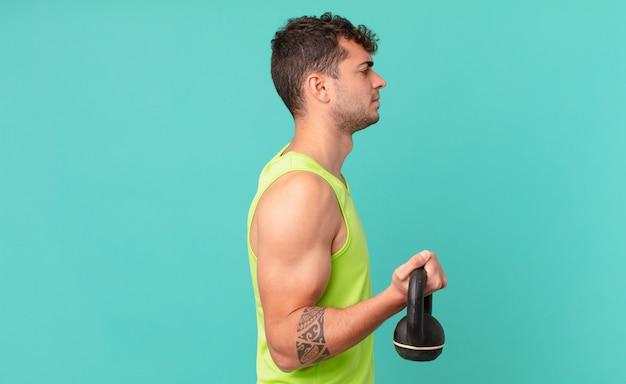 Fitness man op profielweergave die ruimte vooruit wil kopiëren, denken, fantaseren of dagdromen