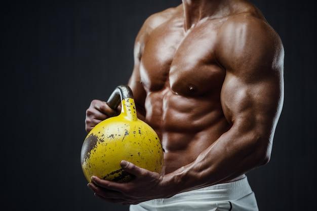 Fitness man oppompen van spieren met kettlebell