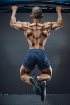Fitness man oppompen van spieren pull ups oefeningen doen