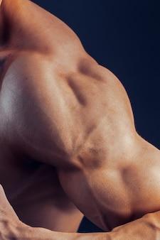 Fitness man ruimte schouder biceps borstspieren triceps bodybuilder op een donkere ruimte toont de fysieke vorm voor lessen in de sportschool