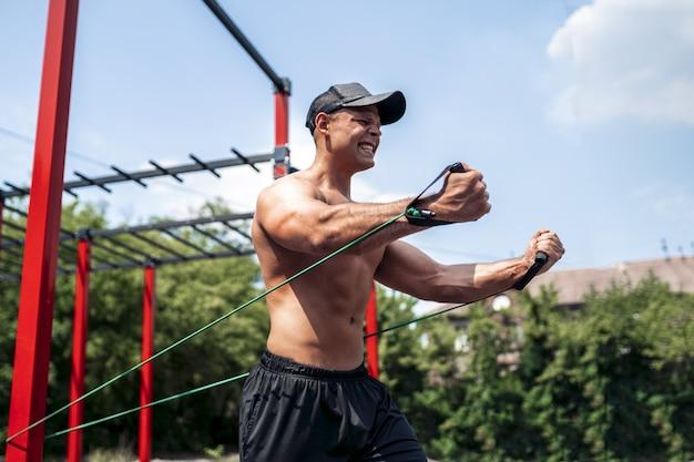 Fitness man training borst met weerstand bands op straat gym werf. outdoor training. lichaamstraining met buiten apparatuur. elastiek elastiek.