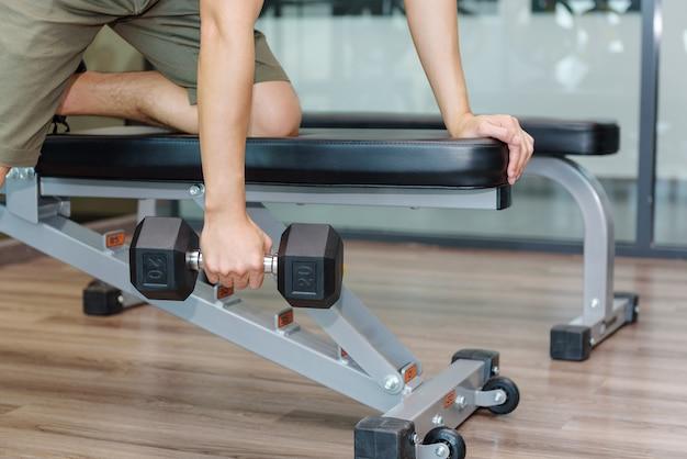 Fitness man traint of oefent door halters op te heffen. in fitnessruimte bij sportgymnastiek.