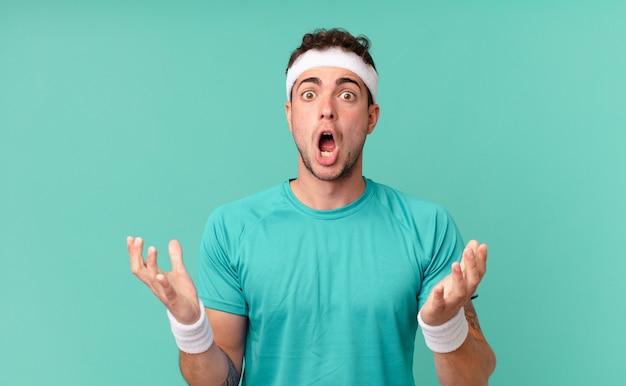 Fitness man voelt zich extreem geschokt en verrast, angstig en in paniek, met een gestresste en geschokte blik