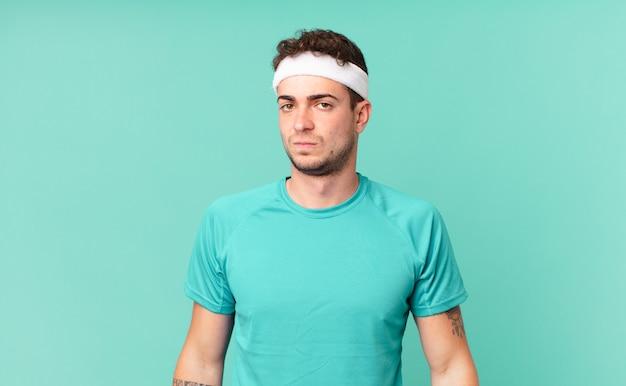 Fitness man voelt zich verdrietig, overstuur of boos en kijkt opzij met een negatieve houding, fronsend in onenigheid