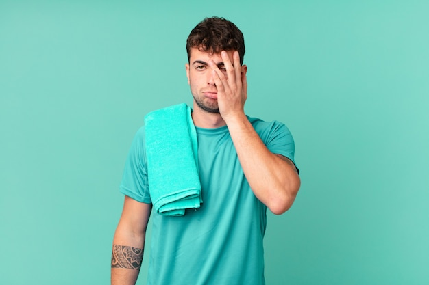 Fitness man voelt zich verveeld, gefrustreerd en slaperig na een vermoeiende, saaie en vervelende taak, gezicht met de hand vasthoudend