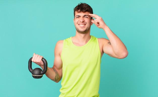Fitness man voelt zich verward en verbaasd en laat zien dat je gek, gek of gek bent
