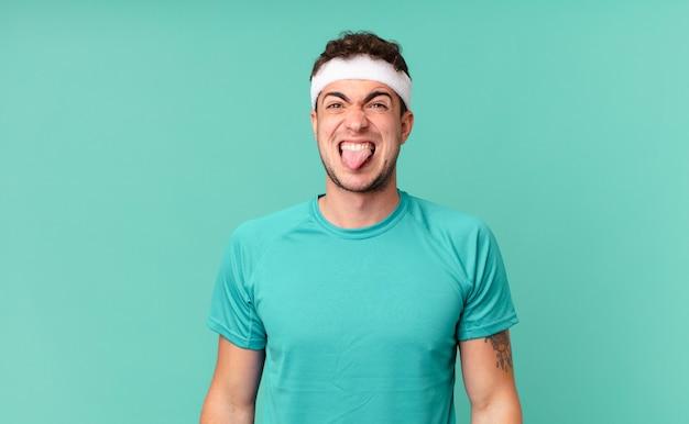 Fitness man walgt en geïrriteerd voelt, tong uitsteekt, een hekel heeft aan iets smerigs en vies