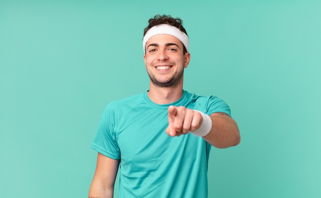 Fitness man wijzend op camera met een tevreden, zelfverzekerde, vriendelijke glimlach, jou kiezen