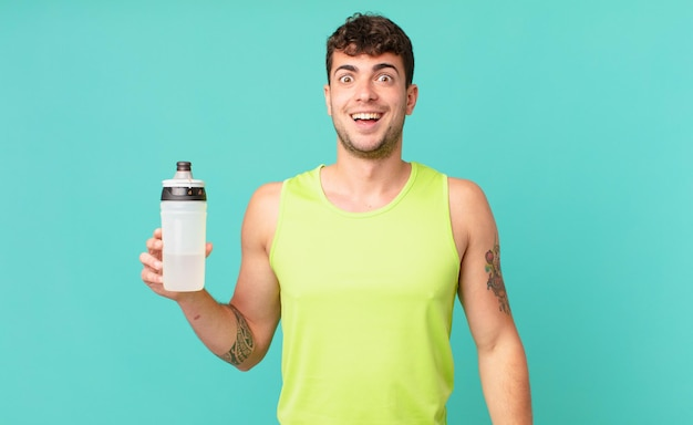 Fitness man ziet er blij en aangenaam verrast uit, opgewonden met een gefascineerde en geschokte uitdrukking