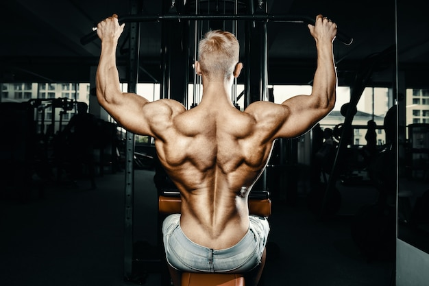 Fitness mannen doen pull-ups oefeningen in de sportschool