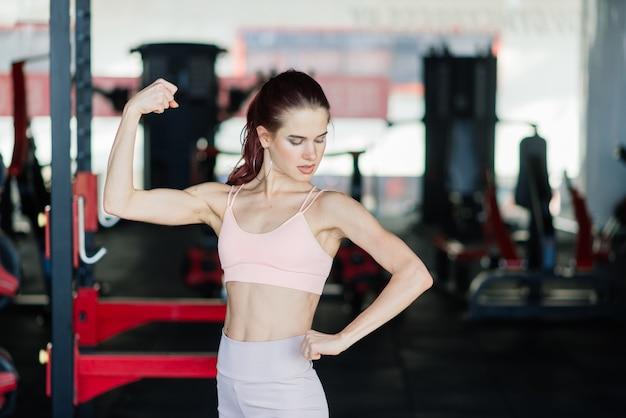 Fitness meisje halter opheffen in de ochtend, fles, sportschool