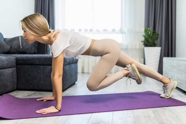 Fitness meisje horloge laptop aerobics regime training video stretch benen heupen squats dragen slipje op mat vloer thuis