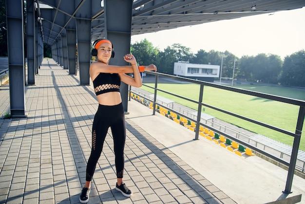 Fitness meisje in legging en tops is sporten in een stadslandschap, opgewarmd voor de training.