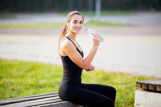 Fitness meisje. jonge mooie vrouw in sportkleding drinkwater in park