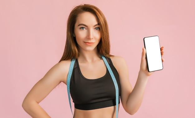 Fitness meisje lacht en houdt een telefoon vast met een mockup en poseert met meetlint in zwarte sportkleding op een roze oppervlak