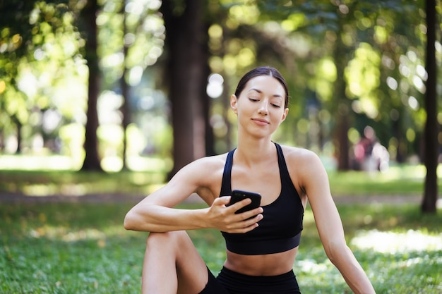 Fitness meisje met een smartphone op natuur achtergrond, geniet van sportopleiding. vrouw met behulp van mobiele telefoon buitenshuis.