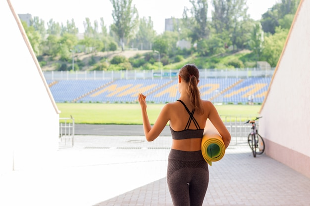 Fitness meisje met yoga mat going on stadium, sport en fitness concept