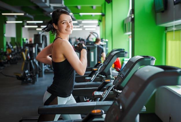 Fitness meisje mooie brunette draait op de loopband ochtend. concept van een gezonde levensstijl.