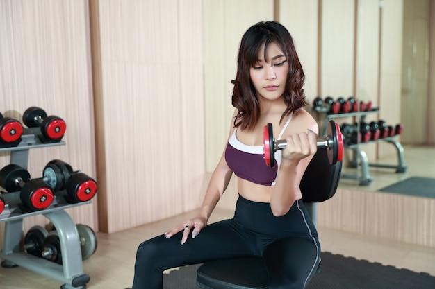 Fitness meisje opheffing halter en training in de sportschool