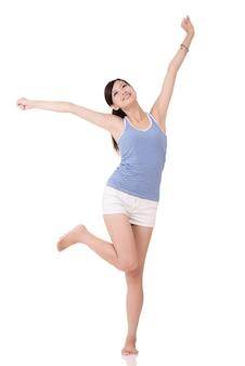 Fitness meisje rekt uit en voel je vrij, volledig lengteportret op witte achtergrond.