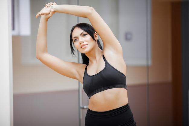 Fitness meisje. sexy atletisch meisje dat in gymnastiek uitwerkt. fitness vrouw doet oefening