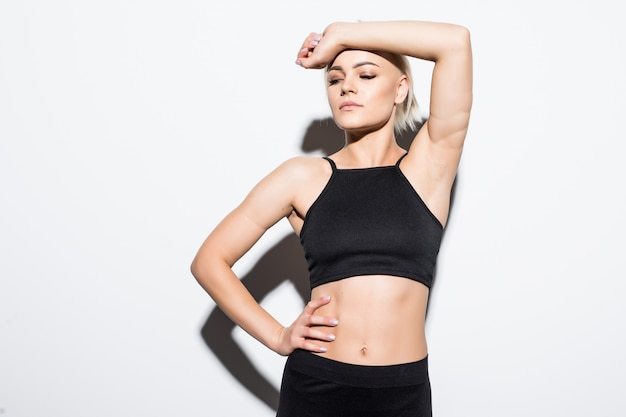 Fitness meisje wordt moe en vermoeid voelen in de studio op wit gekleed in zwarte sportkleding