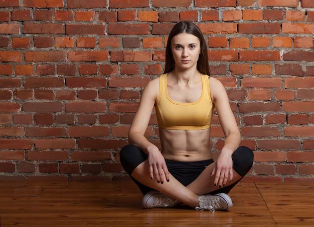 Fitness meisje, zittend op de vloer