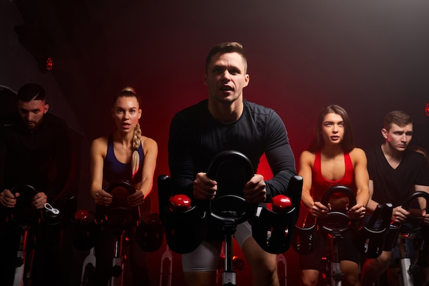 Fitness mensen in een rij trainen met fietsen in een sportschool. sport, levensstijl en gezondheidszorgconcept