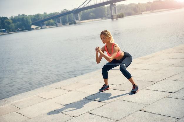 Fitness model. jonge en sterke blonde vrouw in sportkleding trainen met een weerstandsband buiten voor de rivier. sportconcept. fitnessapparatuur