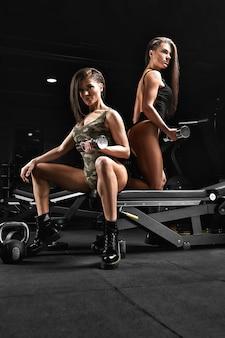 Fitness model tweeling poseren in de sportschool tijdens training