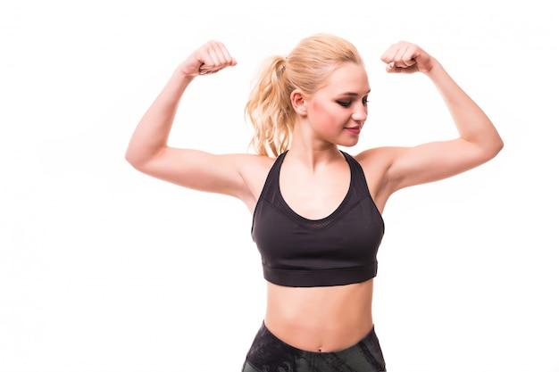 Fitness model van de blonde het jonge vrouw in zwarte sportenbovenkant toont haar cijfer aan
