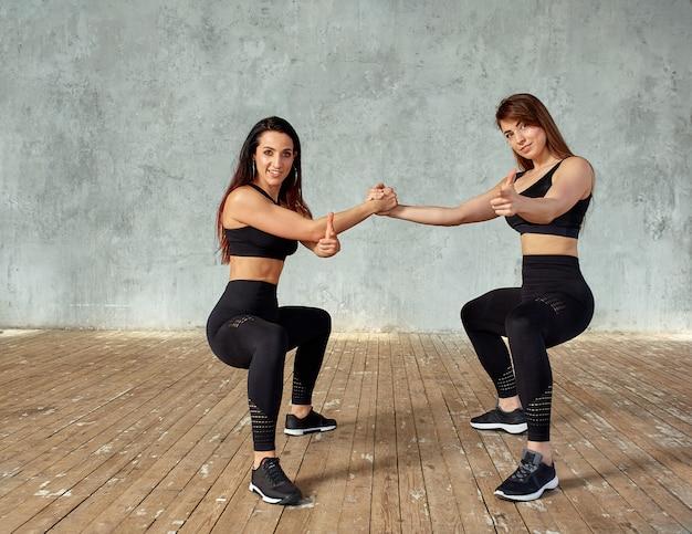 Fitness modellen doen oefeningen met elastiek in een fitness-studio.