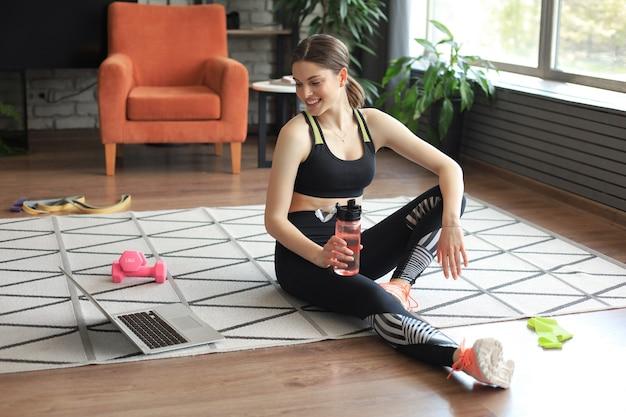 Fitness mooie slanke vrouw zit op de vloer met halters en een fles water met behulp van laptop thuis in de woonkamer. blijf thuis activiteiten.